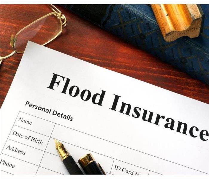 "A white paper with ""Flood Insurance"" as a title, there is a pen and glasses on top of the paper"